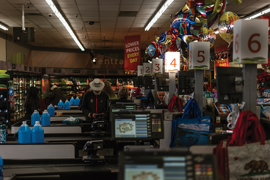 EXPRESS LANE?: The lines down the aisle at our local supermarkets in peak season have less to do with the influx of visitors than the difficulty of hiring enough workers to staff the checkout lanes. Photo by Wade Snider/Moonshine Ink